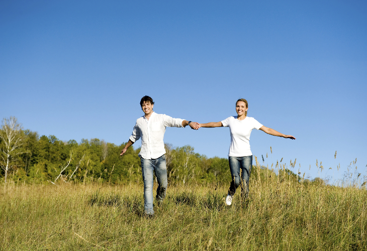 Happy young couple running on summer meadow